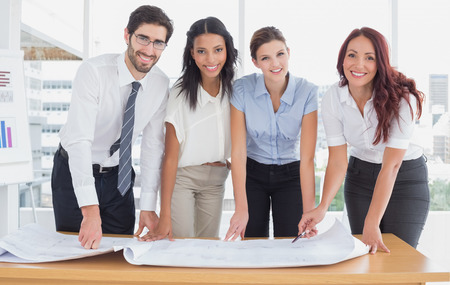 18 to 30s: Business team smiling at camera while holding plans