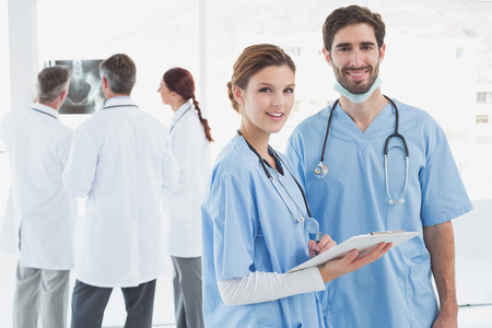 18 to 30s: Nurses holding a file together and smiling at the camera