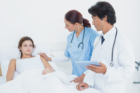 18 to 30s: Doctor holding a tablet computer while talking to his patient Stock Photo