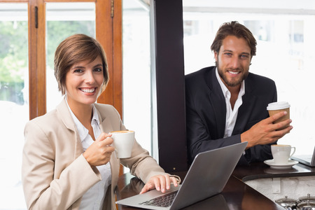 Business people smiling at the camera at the coffee shop photo