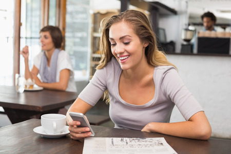 Pretty blonde sending text message at the coffee shop photo