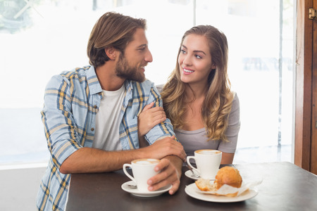 linking together: Happy couple enjoying a coffee at the coffee shop Stock Photo