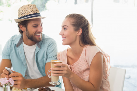 Happy couple enjoying coffee and cake at the coffee shop photo