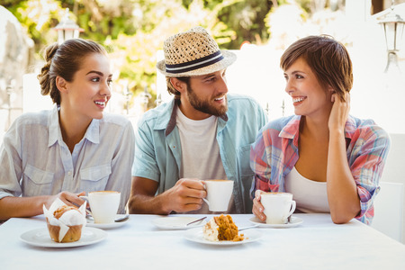 Happy friends enjoying coffee together outside at the coffee shop photo