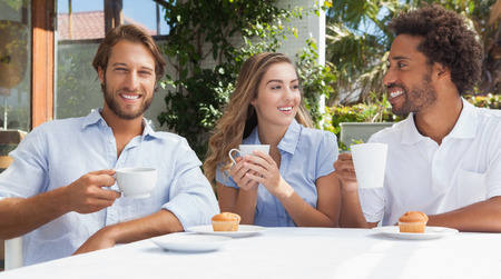 Happy friends having coffee together outside at the coffee shop photo