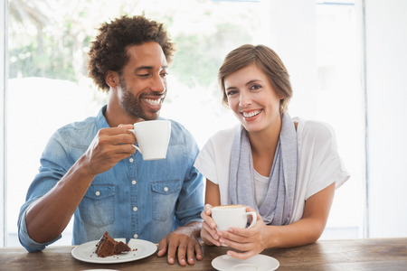 Casual couple having coffee and cake together at the coffee shop photo