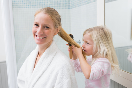 some under 18: Happy mother and daughter brushing hair at home in the bathroom