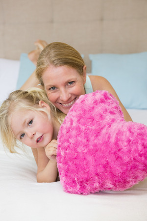 Cute little girl and mother on bed at home in bedroom photo