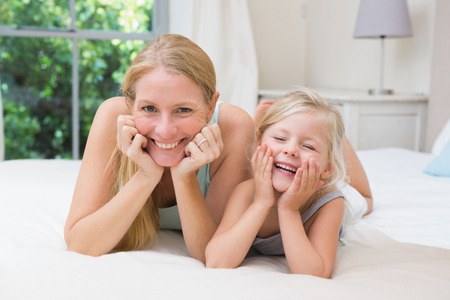 some under 18: Cute little girl and mother on bed at home in the bedroom