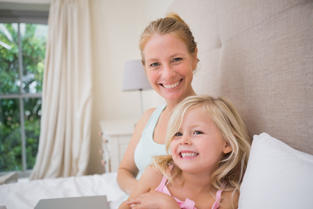 some under 18: Cute little girl and mother on bed using laptop at home in the bedroom
