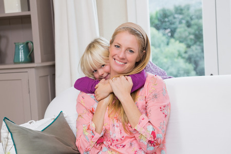 Happy mother and daughter on the couch at home in the living room photo