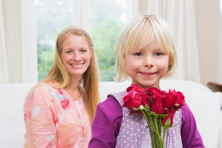 some under 18: Happy woman holding red roses with daughter at home in the living room