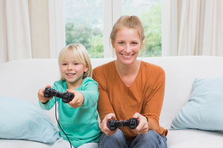 Happy mother and daughter playing video games together on sofa at home in the living room