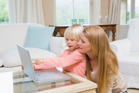 some under 18: Cute daughter and mother using laptop on coffee table at home in the living room