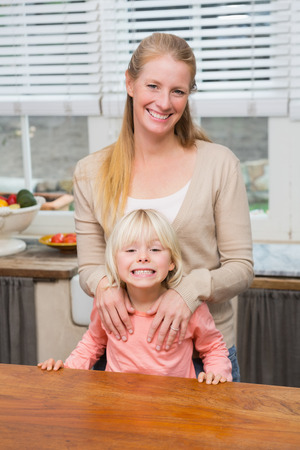 some under 18: Cute daughter and mother smiling at camera at home in the kitchen
