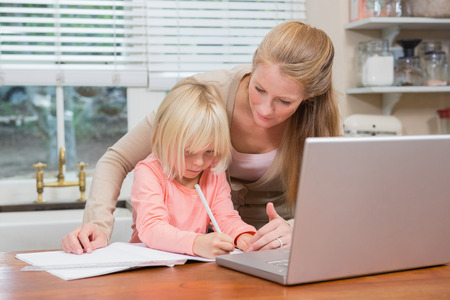some under 18: Cute daughter and mother doing homework at home in the living room Stock Photo