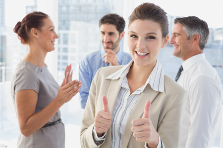 18 to 30s: Businesswoman smiling while at work with co-workers and giving a thumbs up