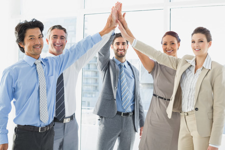 18 to 30s: Employees celebrating a good job with a high five Stock Photo