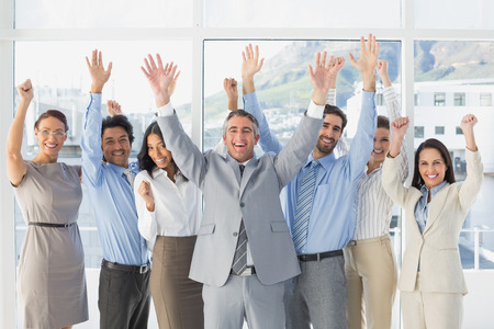 18 to 30s: Cheering workers with raised arms in the office