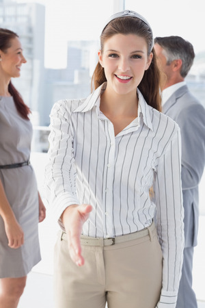 18 to 30s: Smiling business woman offering handshake at work Stock Photo