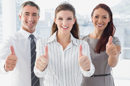 18 to 30s: Smiling businesswoman giving thumbs up with co-workers Stock Photo