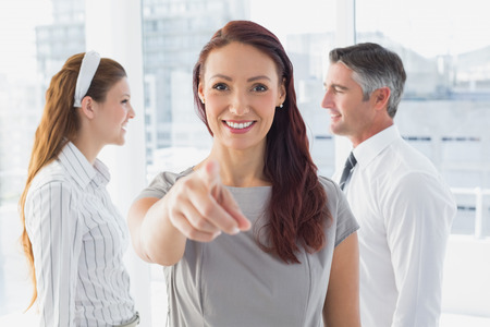 Smiling businesswoman pointing at camera in the office