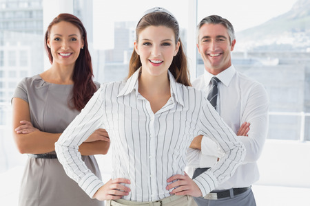 18 to 30s: Smiling businesswoman with hand on hip with co-workers