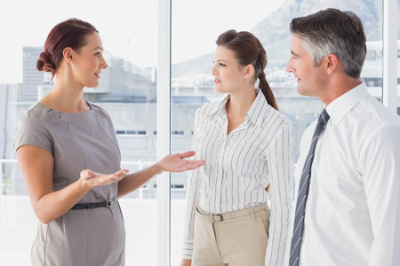 18 to 30s: Businesswoman talking with her co-workers in the office