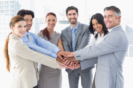 business executive: Business team stacking their hands together while smiling