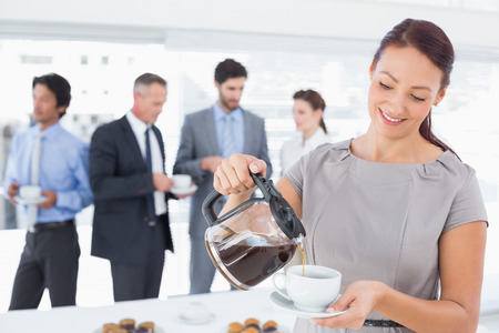 Businessman pouring himself some coffee in work photo