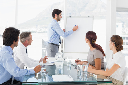Business man die een presentatie geeft aan zijn team