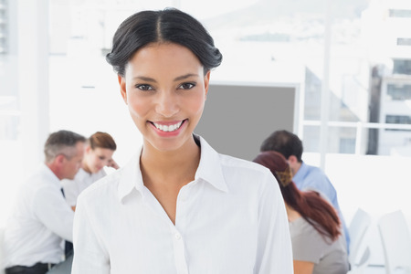18 to 30s: Smiling businesswoman and her colleagues in the office