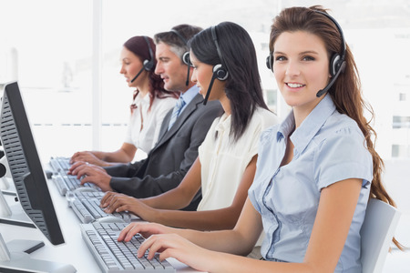 18 to 30s: Employees typing on their computers using headsets