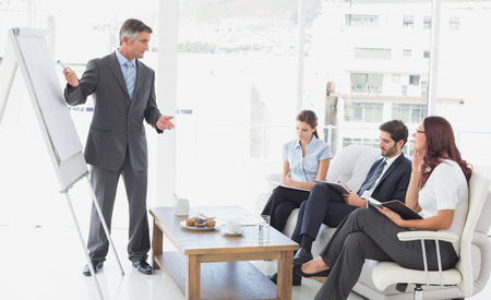 18 to 30s: Businessman giving a presentation to co-workers Stock Photo