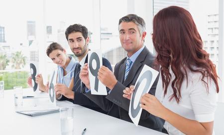votaciones: Equipo de negocios dando calificaciones en una oficina Foto de archivo