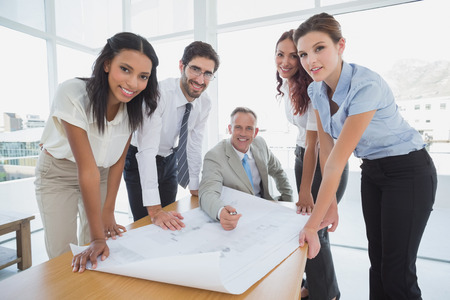 Business people smiling at camera while working on plans photo