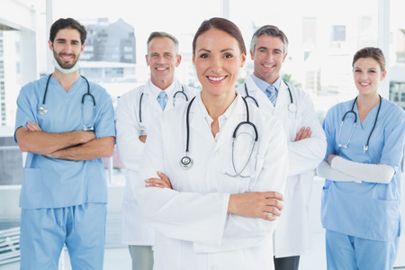 man doctor: Smiling doctor with fellow doctors standing behind her Stock Photo