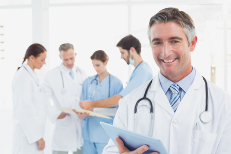 18 to 30s: Doctor smiling at the camera as he uses a tablet