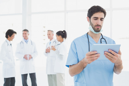 Serious doctor looking at tablet with co-workers behind him photo