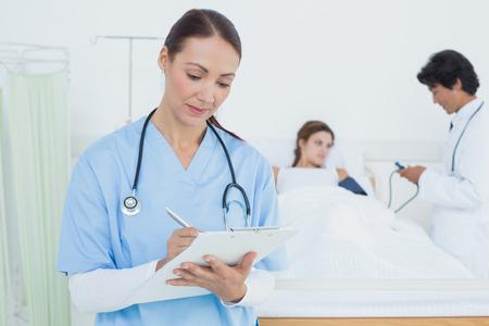 의사와 환자가 그녀의 뒤에 의료 차트 작성 간호사