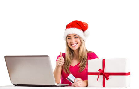 Festive blonde shopping online with laptop on white background photo