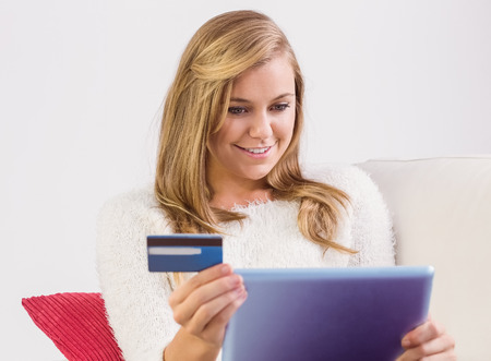 Pretty blonde shopping online with tablet pc at home in the living room photo