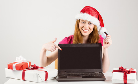 Festive redhead shopping online with laptop on white background photo