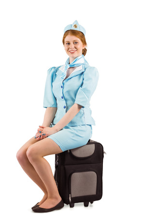 Pretty air hostess smiling at camera on white background photo