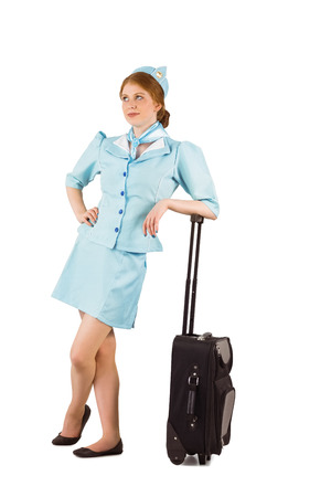 Pretty air hostess leaning on suitcase on white background photo