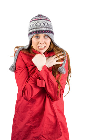 Cold redhead wearing coat and hat on white background photo