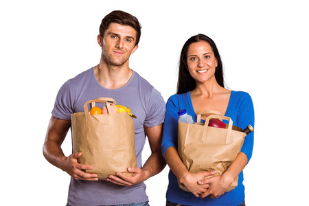 Young couple holding grocery bags on white background photo