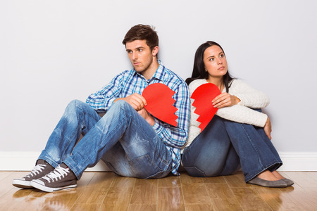 Young couple sitting on floor with broken heart at home Stock Photo