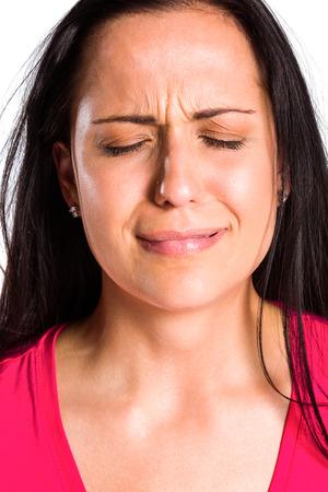 desolaci�n: Morena joven triste llorando en cerca sobre fondo blanco Foto de archivo