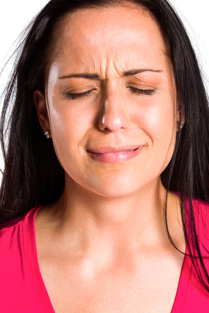 wistfulness: Sad young brunette crying in close up on white background Stock Photo